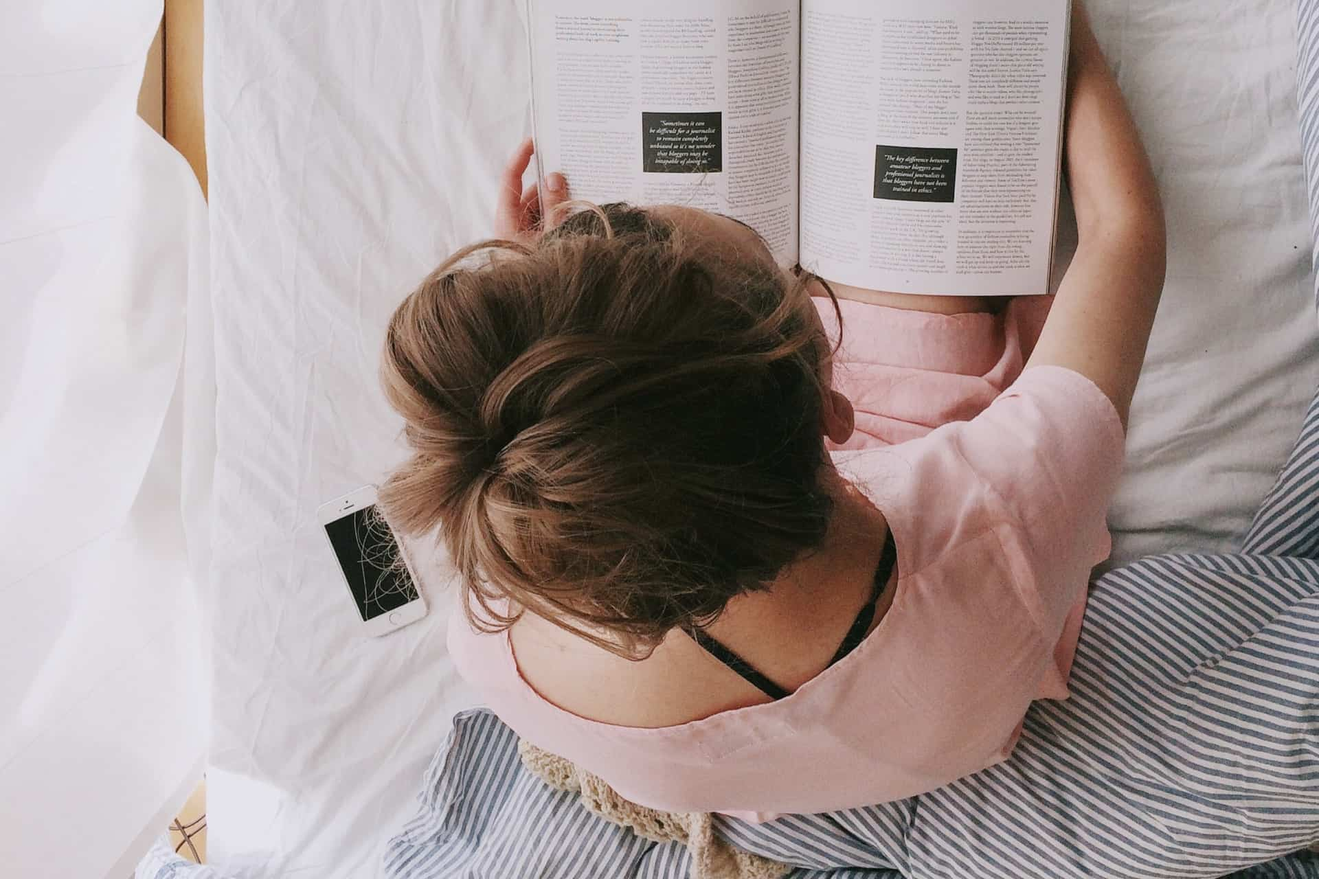 woman-in-pink-dress-sitting-on-bed-while-reading-698158